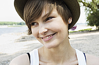 Germany, Rheinland, Young woman with cap, smiling - LFOF000119