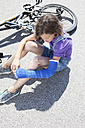 Germany, Bavaria, Wounded girl sitting on road after bicycle accident - MAEF003572