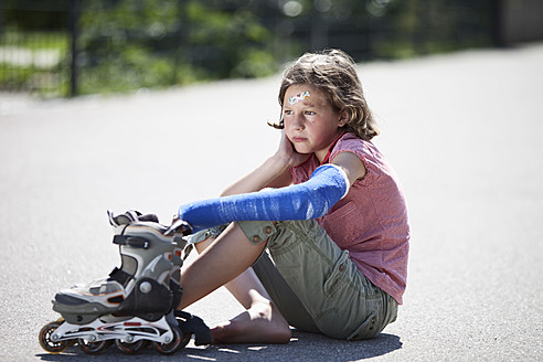 Germany, Bavaria, Wounded girl sitting on road after inline-skating accident - MAEF003579