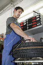 Germany, Ebenhausen, Mechatronic technician working on tyre in car garage - TCF001620