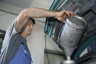 Germany, Ebenhausen, Mechatronic technician pouring oil in car at car garage - TCF001644