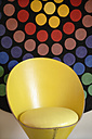 Germany, Upper Bavaria, Munich, Designed chair in new house with multicoloured background - TC001693