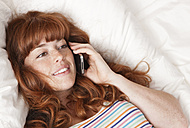 Germany, Berlin, Close up of young woman talking on cell phone, smiling - WESTF016887
