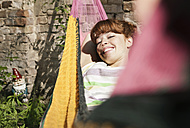 Germany, Berlin, Young woman in hammock, smiling, portrait - WESTF016902