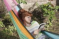 Germany, Berlin, Young woman reading book in hammock, smiling - WESTF016905