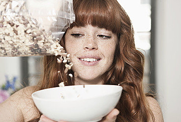 Germany, Berlin, Close up of young woman preparing cereals, smiling - WESTF016911