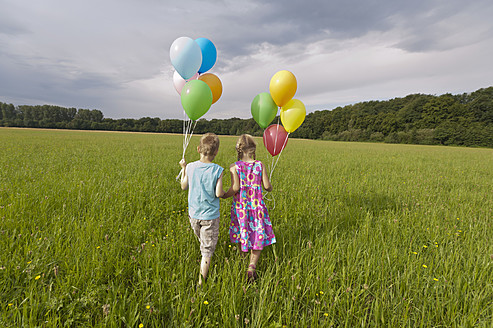 Germany, North Rhine-Westphalia, Hennef, Girl and boy holding balloons and walking in meadow - KJF000128