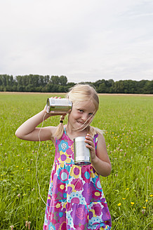 Germany, North Rhine-Westphalia, Hennef, Girl standing in meadow and playing with tin can phone - KJF000136