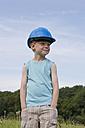 Germany, North Rhine-Westphalia, Hennef, Boy with construction worker helmet standing in meadow - KJF000139