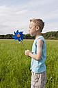 Germany, North Rhine-Westphalia, Hennef, Boy blowing wind mill in meadow - KJF000141
