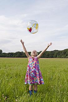 Germany, North Rhine-Westphalia, Hennef, Girl throwing beach ball globe in meadow - KJF000147
