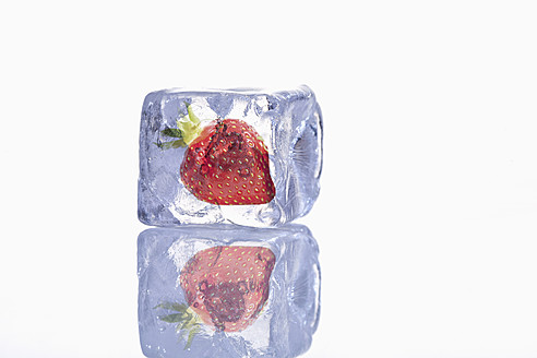 Frozen strawberry in ice cube with reflection on glass - TSF000334