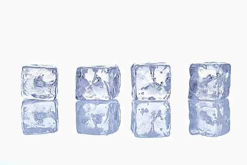 Four ice cubes in row with reflection on glass - TSF000341