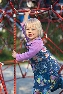 Germany, Munich, Girl climbing on climbing frame in playground, smiling, portrait - HSIF000127