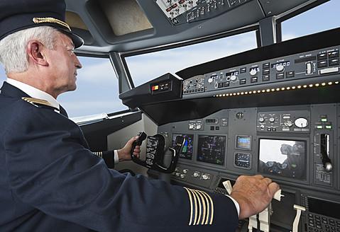Germany, Bavaria, Munich, Senior flight captain piloting aeroplane from airplane cockpit - WESTF017017