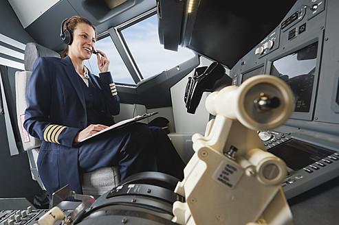 Germany, Bavaria, Munich, Woman flight captain piloting aeroplane from airplane cockpit - WESTF017035
