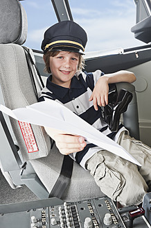 Germany, Bavaria, Munich, Boy wearing captain's hat and holding paper plane in airplane cockpit - WESTF017092