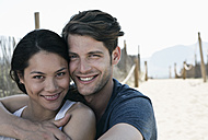Spain, Majorca, Young man embracing woman on boardwalk at beach, portrait - WESTF017110