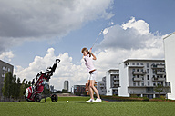 Germany, Bavaria, Munich, Young woman playing city-golf - MAEF003713