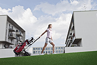 Germany, Bavaria, Munich, Young woman carrying golf cart - MAEF003695