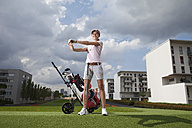 Germany, Bavaria, Munich, Young woman stretching in city-golf ground - MAEF003699