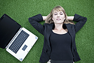 Germany, Bavaria, Munich, Businesswoman relaxing on lawn besides laptop - MAEF003708