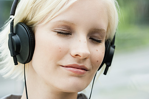 Germany, Bavaria, Munich, Young woman listening music - SPOF000053