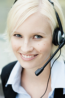 Germany, Bavaria, Munich, Young woman with headset, smiling, portrait - SPOF000004