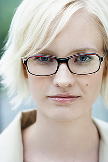 Germany, Bavaria, Munich, Young woman with spectacles, portrait, smiling - SPOF000012