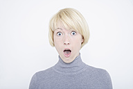 Close up of shocked young woman against white background, portrait - TCF001761