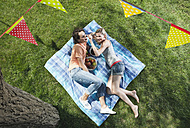 Italy, Tuscany, Young couple lying on picnic blanket with food and flag line hanging above - PDF000195
