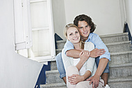 Italy, Tuscany, Young couple sitting on stairway of hotel, portrait - PDF000252
