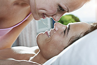 Italy, Tuscany, Young couple romancing on bed in hotel room - PDF000257