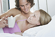 Italy, Tuscany, Young man holding coffee cup beside woman while lying on bed in hotel room - PDF000260