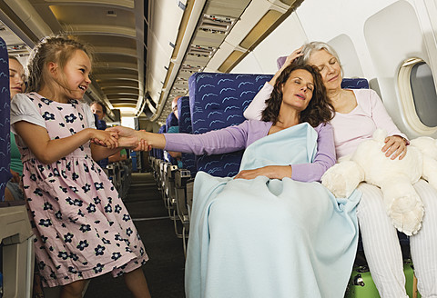 Germany, Munich, Bavaria, Women sleeping and girl pulling woman's hand in economy class airliner - WESTF017203