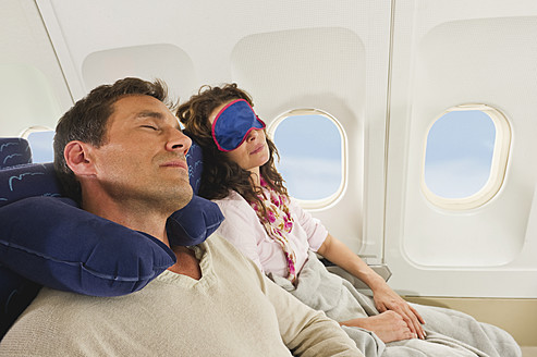 Germany, Munich, Bavaria, Mid adult couple wearing sleep mask and sleeping in economy class airliner - WESTF017209