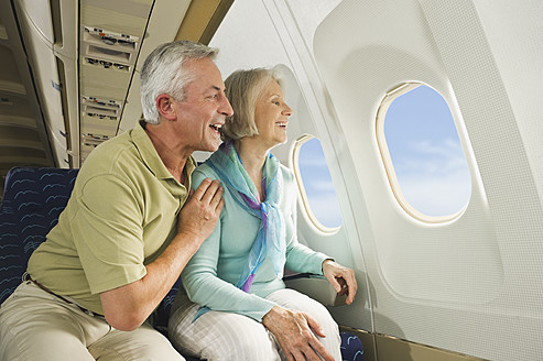 Germany, Munich, Bavaria, Senior couple looking out through window in economy class airliner - WESTF017227