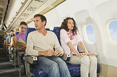 Germany, Munich, Bavaria, Passengers reading book in economy class airliner - WESTF017260