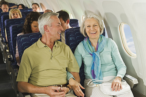 Germany, Munich, Bavaria, Group of passengers in economy class airliner, smiling - WESTF017263