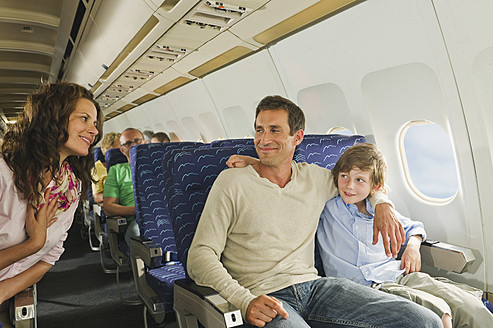 Germany, Munich, Bavaria, People talking in economy class airliner - WESTF017269