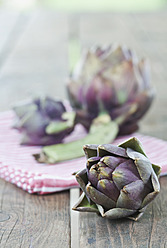 Italy, Tuscany, Magliano, Close up of artichokes with napkin on wooden table - WESTF017343