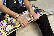 Germany, Düsseldorf, Close up of skateboarder sitting on edge of skatebowl and holding his deck - KJF000153