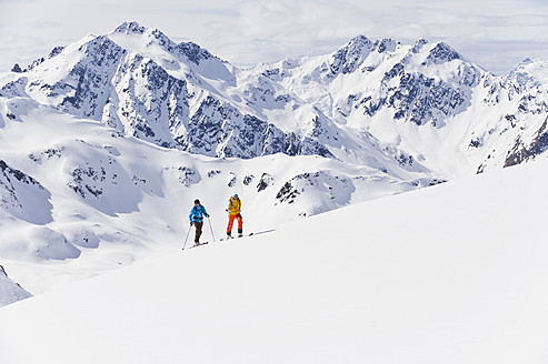 Austria, Stuben, Young couple doing telemark skiing on arlberg mountain - MIRF000299