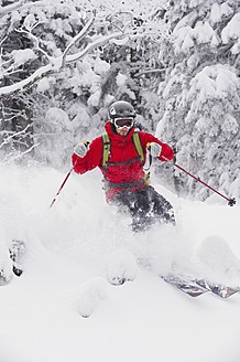 Germany, Bavaria, Young man doing telemark skiing in Herzogstand mountain forest - MIRF000314