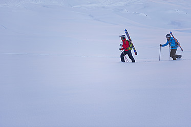 Austria, Zuers, Telemark skiers walking in Arlberg mountain snow - MIRF000332