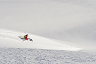Austria, Zuers, Young man doing telemark skiing on Arlberg mountain - MIRF000335