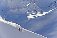 Austria, Zuers, Young man doing telemark skiing on Arlberg mountain - MIRF000344