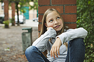 Germany, Berlin, Girl sitting in front of red brick wall - WESTF017472