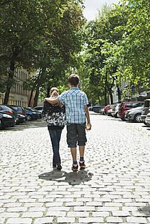 Germany, Berlin, Boy and girl walking in street as couple - WESTF017496