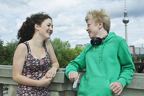 Germany, Berlin, Teenage couple with headphone on bridge - WESTF017526